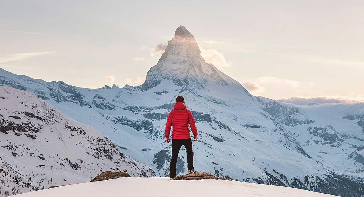 Ein Mann steht auf einer Felskuppe und sieht sein Ziel, die Bergspitze, vor sich. Lerne mit NLP wie du alles erreichen kannst, was du möchtest.