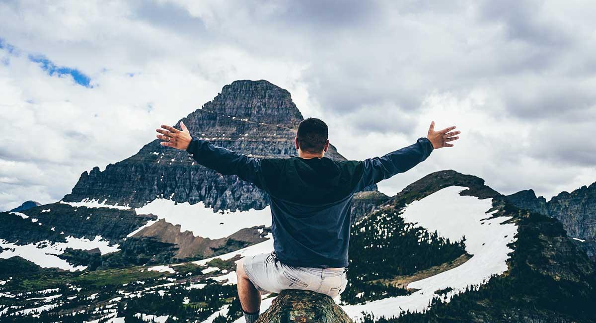 Mann mit ausgebreiteten Armen in den Bergen. Er strahlt Selbstbewusstsein aus.