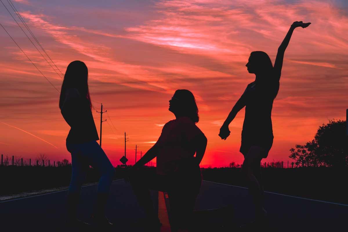 Eine Gruppe von drei Menschen, die im Halbkreis stehen und Tanzen. Sie sind bereist beliebt.
