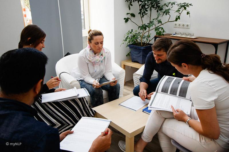 Es werden TeilnehmerInnen abgebildet, die gemeinsam in der Gruppe verschiedene Inhalte ausarbeiten