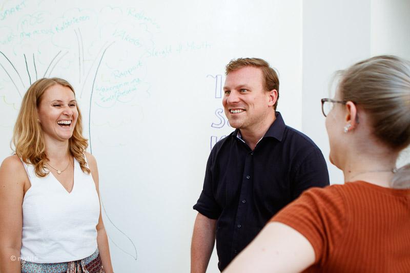 Hier sieht man Teilnehmerinnen, die gemeinsam mit Trainer Philipp Effenberger lachen.